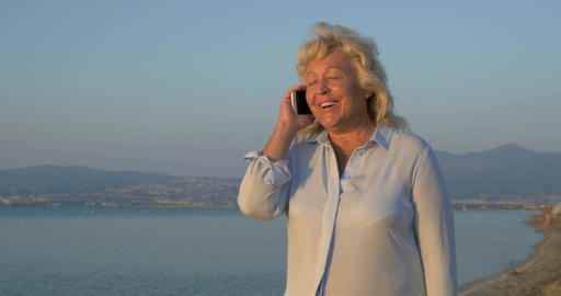 On the sea coast city of Perea, Greece is walking woman and talking on mobile ph Footage