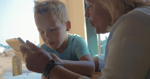 In city of Perea, Greece sits a grandmother with her grandson and teaches him ho Footage