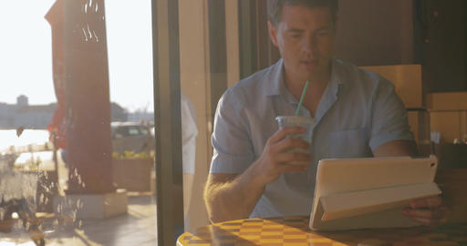 Young man searching something in tablet drinking iced tea from tubule Footage