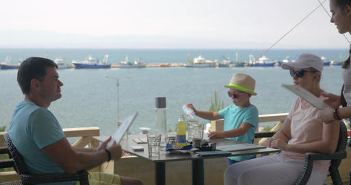 On the sea coast of city Perea, Greece a young family sits in cafe Footage