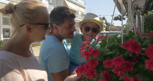 Mother father and son snuff red flowers from hanging flower bed Piraeus, Greece Footage