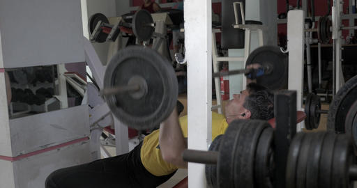 Sportsman flexing chest muscles on bench Live Action
