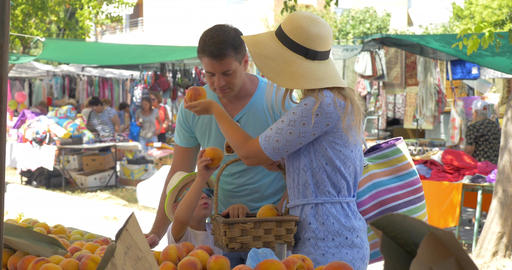 Young family in market of Thessaloniki, Greece choose peaches Footage