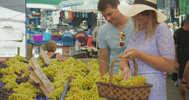couple choosing grapes and speaking with smile on outdoor market. Thessaloniki,  Footage