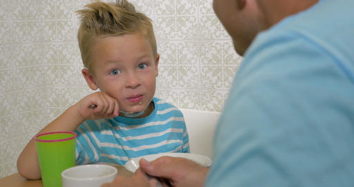 Son speaking with father and eat using a spoon and smiling Footage