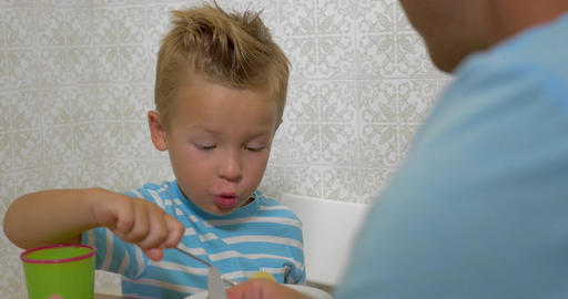 Father teaching son to use a spoon during eating Footage
