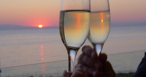 clinking glasses of champagne against sunset sea Piraeus, Greece Live Action