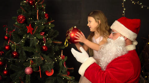 Santa Claus and a little girl decorate a Christmas tree. Santa holds the girl in his arms Live Action