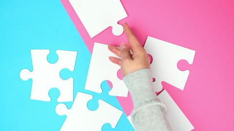 empty paper white pieces of puzzles in female hands, puzzle connected, colorful background Live Action