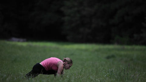 A young woman does yoga exercises in the grass Footage
