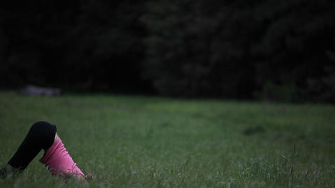 A young woman does yoga exercises in the grass Stock Video Footage