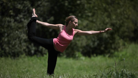 A woman does yoga exercises in a field Stock Video Footage