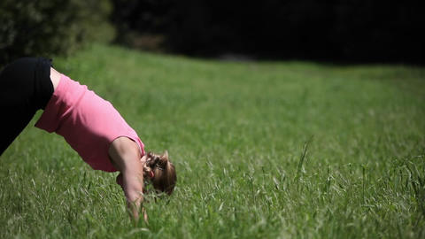 A woman does yoga poses outside in the grass Stock Video Footage