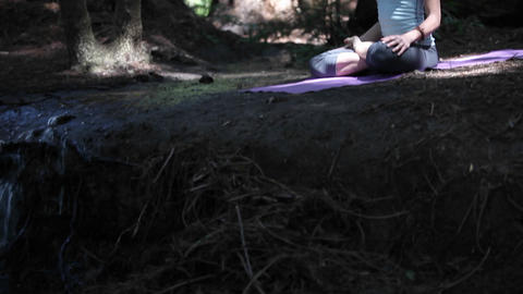 A woman practices yoga near a river Footage
