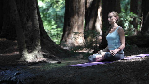 A woman practices yoga near a river Stock Video Footage