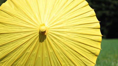 A young woman opens a yellow parasol and twirls it around... Stock Video Footage