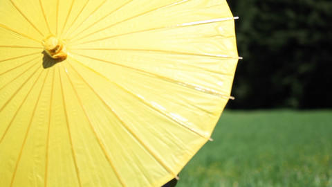 A young woman opens a yellow parasol and twirls it around her head Footage