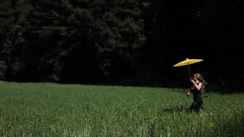 A young woman runs through a grassy field carrying a yellow parasol Footage