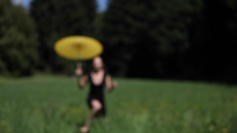A woman with an umbrella runs through a field Stock Video Footage