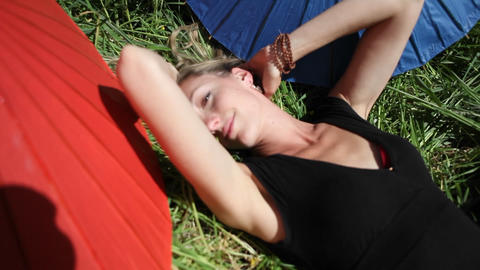 A woman lays out on the grass in the sun surrounded by... Stock Video Footage