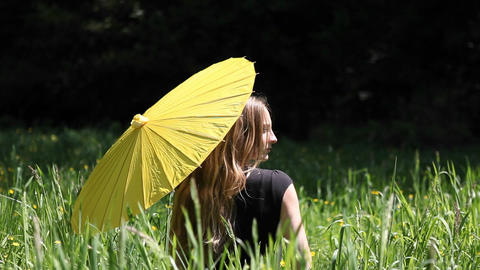 A woman sits in a tall grassy field with an umbrella Footage