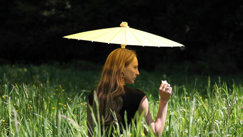 A woman sits on the ground delicately caressing a blade of grass Footage