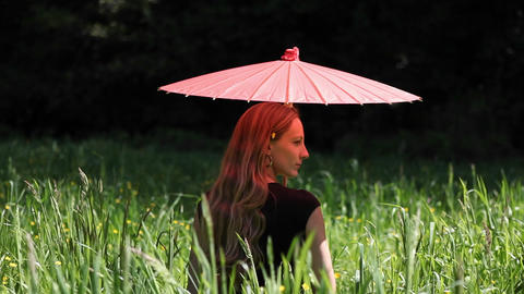 A woman with an umbrella is sitting in a field Footage