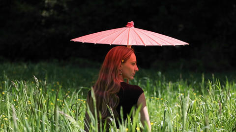 A woman with an umbrella is sitting in a field Stock Video Footage