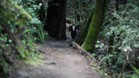 A woman runs through a wooded area Footage