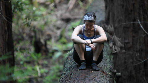 A young woman sits on a fallen log in a forest, puts her... Stock Video Footage
