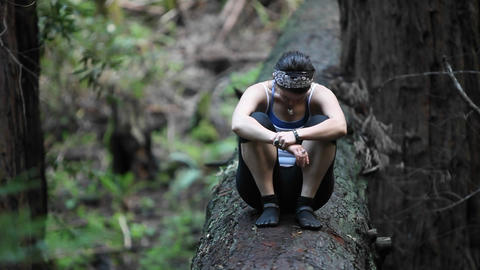 A young woman sits on a fallen log in a forest, puts her head down, then lifts it up Footage