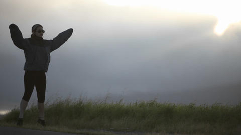 A young woman exercises at the side of a road Stock Video Footage