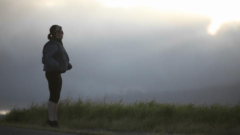 A young woman exercises at the side of a road Footage