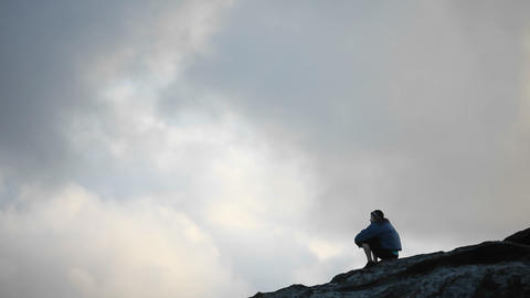 A man sits atop of an elevated area and takes in the view Stock Video Footage