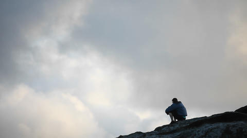 A man sits atop of an elevated area and takes in the view Footage