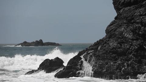 Ocean waves crash against boulders Stock Video Footage