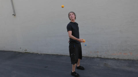 A man juggles three orange balls using his hands and feet Stock Video Footage