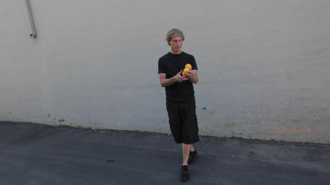 A man juggles three orange balls using his hands and feet Footage