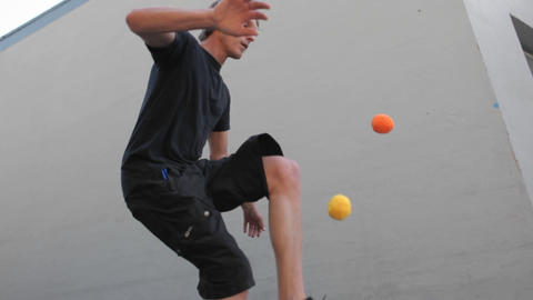 A man juggles balls with his feet Footage