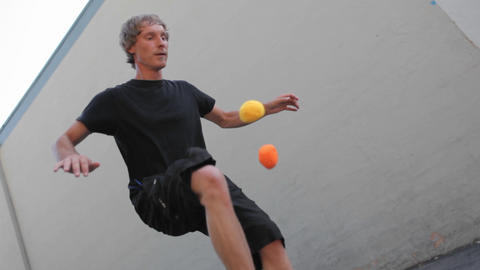 A man juggles balls with his feet Stock Video Footage
