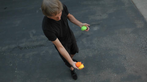 A man juggle balls on his arms, hands and feet Stock Video Footage