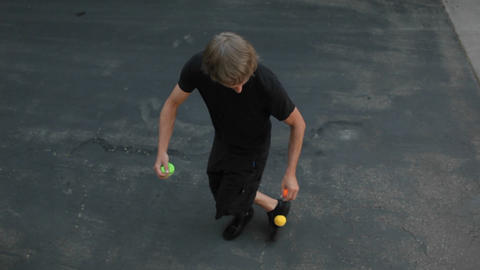A man does a juggling act in the street with three... Stock Video Footage