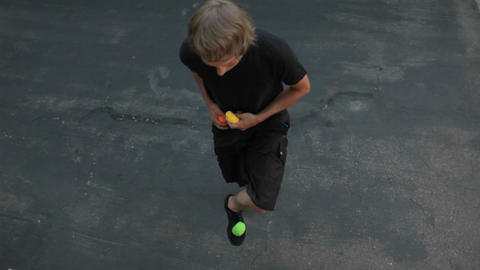 A man does a juggling act in the street with three colored balls Footage