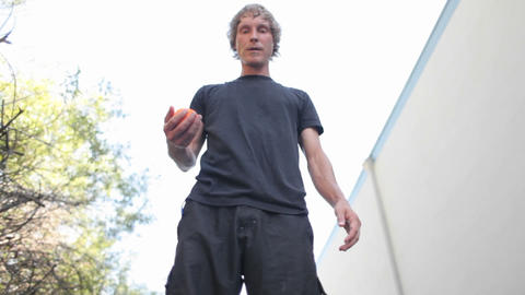 A man does tricks juggling one ball with his feet Stock Video Footage