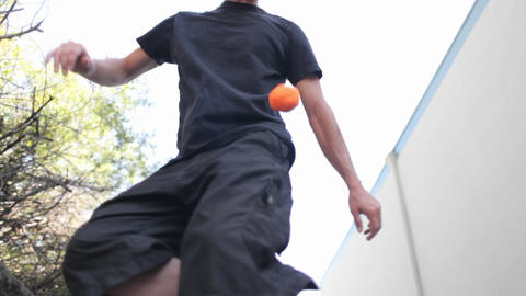 A Man Does Tricks Juggling One Ball With His Feet stock footage