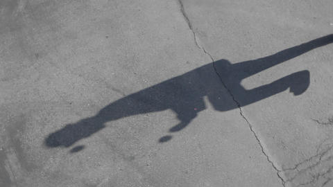 The shadow of a man juggling balls is seen on the sidewalk Footage