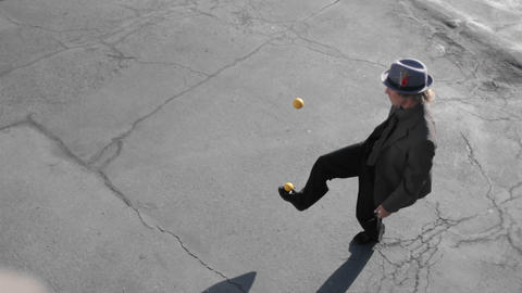 A man juggles two balls with his feet Footage