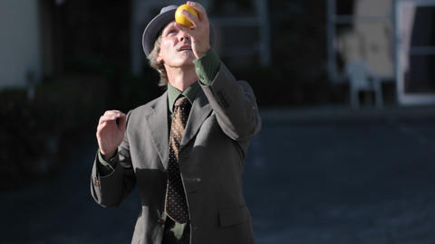 A man does a juggling act using three orange balls Stock Video Footage