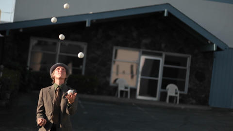 A man starts juggling six balls and drops them all Footage