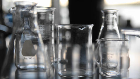 Laboratory glass ware sits on top of a labs counter Stock Video Footage